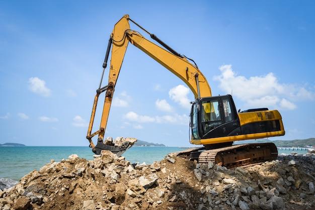 Cantiere di lavoro di pietra della pietra dell'escavatore scavatore dell'escavatore a cucchiaia rovescia sull'oceano del mare della spiaggia