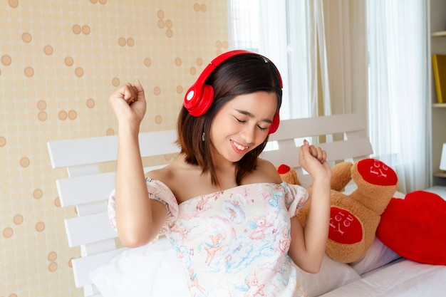 Canzone d'ascolto della giovane donna graziosa con la cuffia