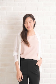 Capelli castani lunghi della bella donna graziosa asiatica che sorridono e che affrontano la sua vista laterale con indosso una maglietta nera e jeans che stanno positng sulla parete di colore beige.
