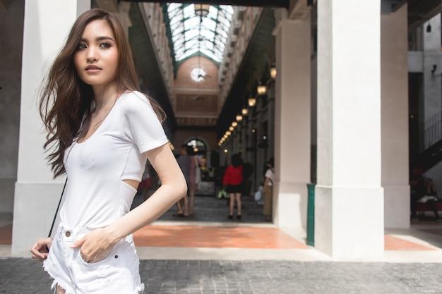 Capelli castani ricci delle donne che portano una camicia bianca e che sorridono.