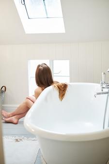 Capelli commoventi della bella giovane donna, guardanti fuori la finestra. bel bagno