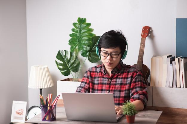 Capelli corti della gente asiatica che lavora al computer portatile