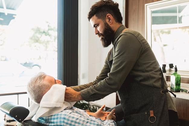 Capelli di spugna del parrucchiere del cliente maschio senior
