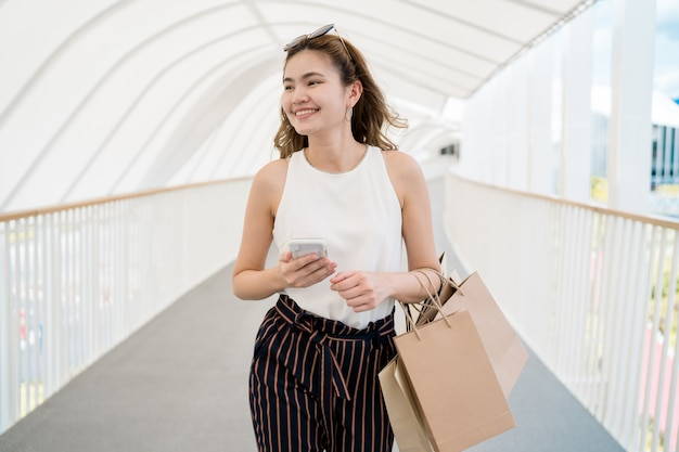 Capelli lunghi bella ragazza sta felicemente facendo shopping nel centro commerciale di strada