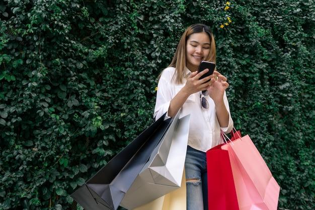 Capelli lunghi della bella ragazza sta comperando felicemente al centro commerciale della via, tiene parecchi sacchi di carta e telefono cellulare, spazio leggero della copia del bokeh la foto.