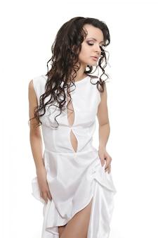 Capelli ondulati e ricci lunghi della bella sposa bianca da portare sexy del vestito isolati su bianco