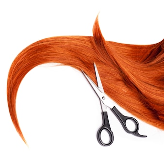 Capelli rossi brillanti e cesoie per capelli isolato su bianco