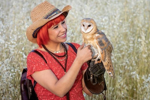 Capelli rossi donna con un gufo bianco sul braccio