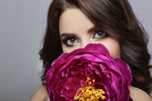 Capelli scuri della bella ragazza e grande fiore vicino al fronte