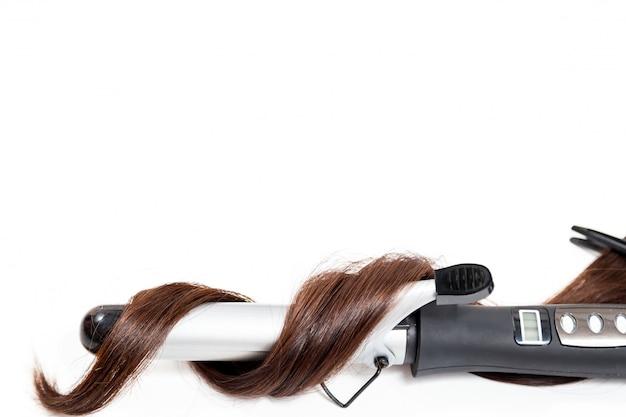 Capelli scuri ricci con un ferro arricciacapelli isolato su sfondo bianco