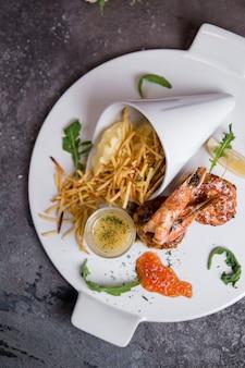 Capesante di pesce con caviale su un piatto bianco su grigio
