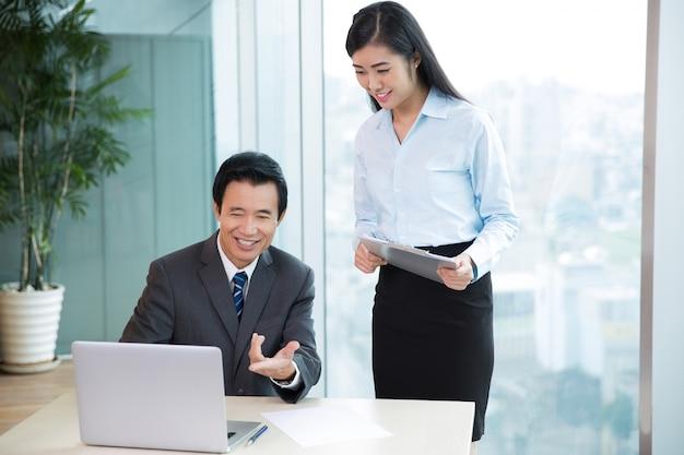 Capo asian discutere idee con assistente femminile