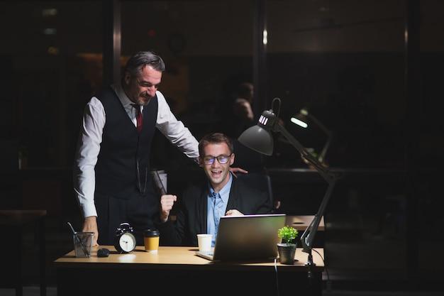 Capo caucasico che lavora tardi stand con il collega in ufficio durante la notte. sguardo dell'uomo di affari al computer portatile con il collega felice di successo con il lavoro. lavoro a tarda notte e concetto di lavoro straordinario