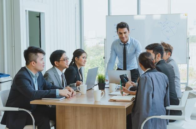 Capo dell'uomo d'affari che presenta per lavorare mentre incontrando i colleghi in ufficio.