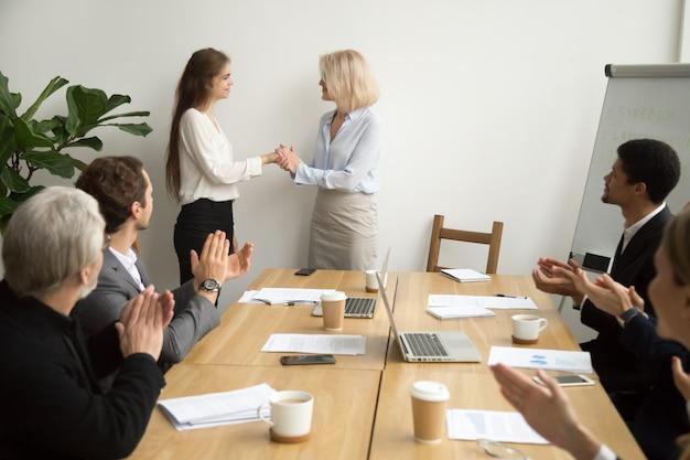 Capo senior della donna di affari che promuove ringraziando impiegato femminile mentre squadra applaude