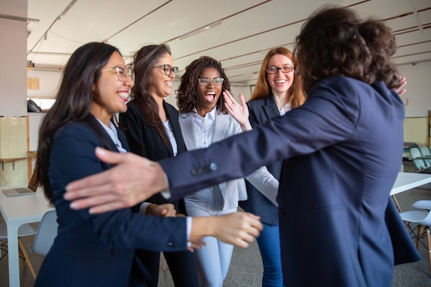 Capo squadra che abbraccia i suoi colleghi più giovani felici