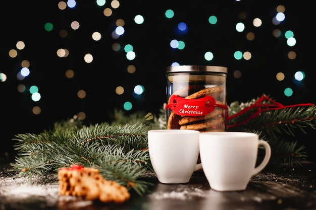 Capodanno e decorazioni natalizie. bottiglia con biscotti al cioccolato e tazze per il tè