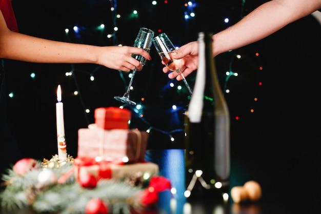 Capodanno e decorazioni natalizie. le persone rumoreggiavano bicchieri con champagne