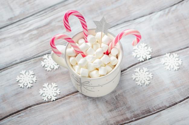 Capodanno o natale. composizione con marshmallow e bastoncini di zucchero su un fondo di legno.