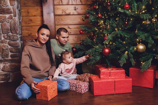 Capodanno o natale, ritratto di una bella famiglia, papà, mamma e figlia vicino all'albero di capodanno, sera di natale, una famiglia tenera e felice in inverno, il padre tiene in braccio la figlia.