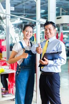 Caposquadra asiatico in fabbrica tessile dando formazione
