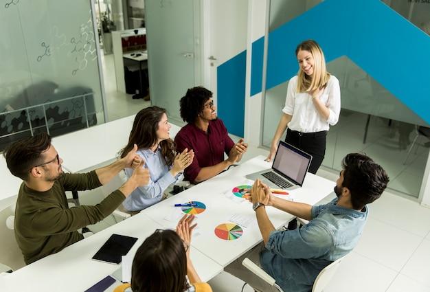 Caposquadra piuttosto femminile parlando con gruppo di persone di razza mista in ufficio