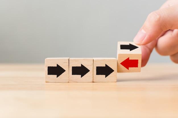 Capovolgi il blocco di cubi di legno con la freccia rossa rivolta nella direzione opposta, frecce nere, uniche, pensa diversamente, individuo e in piedi fuori dal concetto di folla