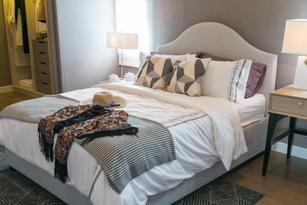 Cappelli e cuscini da donna sul letto.