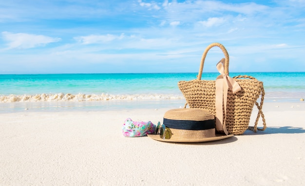 Cappelli e occhiali posizionati sulla spiaggia e sul mare regalano una vacanza estiva all'insegna del relax