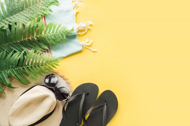 Cappellino da spiaggia in paglia, occhiali da sole, infradito su giallo