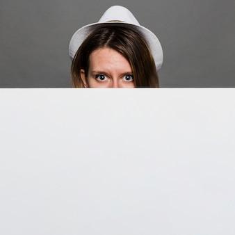 Cappello bianco d'uso della donna che dà una occhiata attraverso la carta in bianco bianca contro la parete grigia