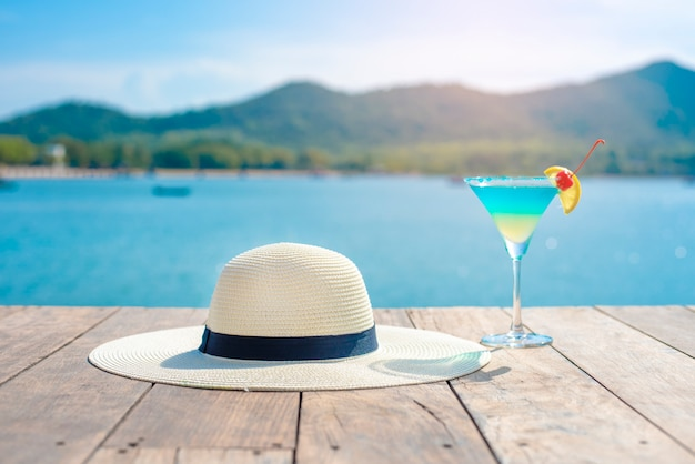 Cappello bianco ed estate bevendo sulla spiaggia