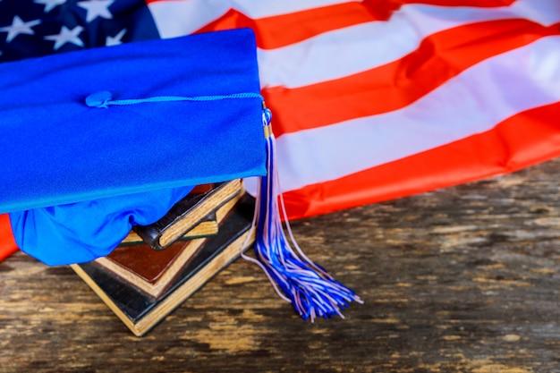 Cappello blu di graduazione sui libri con il fondo della bandiera americana