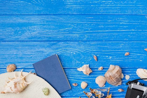 Cappello con fotocamera tra conchiglie e barca giocattolo