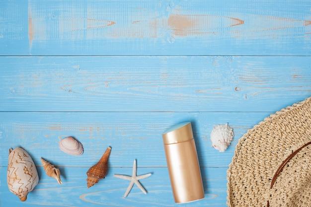 Cappello, crema solare e guscio sul blu
