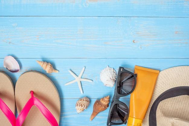 Cappello, crema solare, occhiali da sole, pantofole e guscio blu