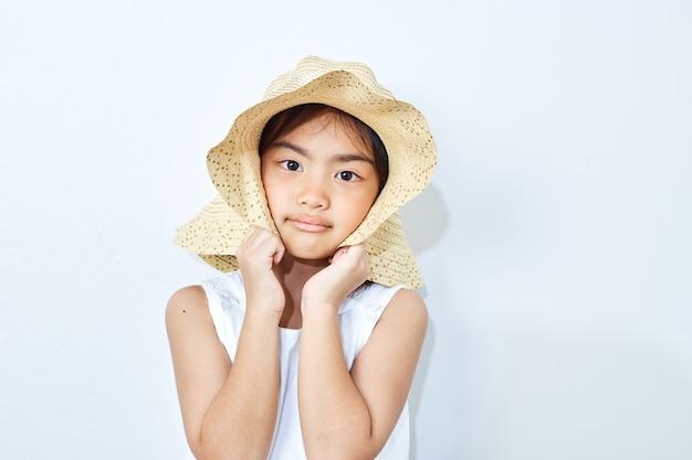 Cappello d'uso della ragazza esile asiatica su fondo bianco.