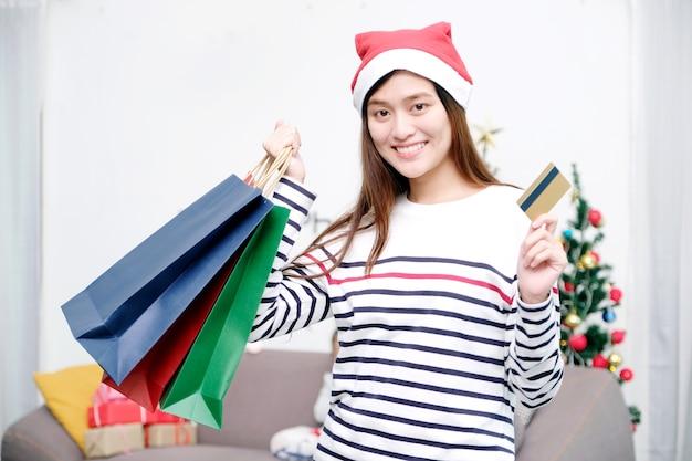 Cappello d'uso di natale della giovane donna asiatica sveglia che sorride mentre tenendo i sacchetti della spesa