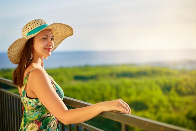 Cappello da portare della donna che osserva al mare