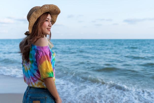 Cappello da portare della donna che si leva in piedi sulla spiaggia del mare