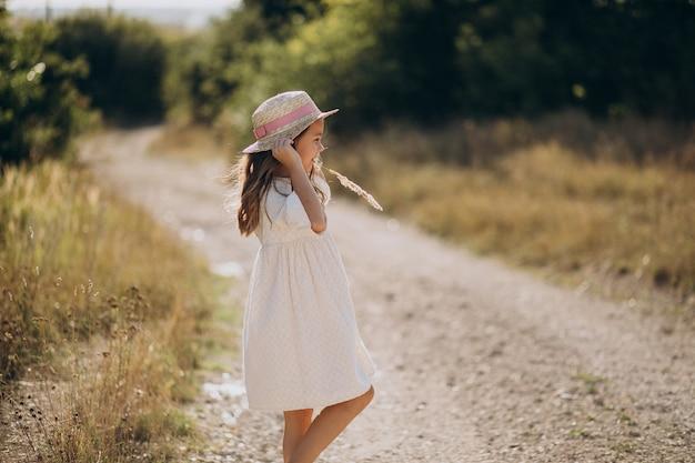 Cappello da portare della ragazza sveglia che cammina nel prato