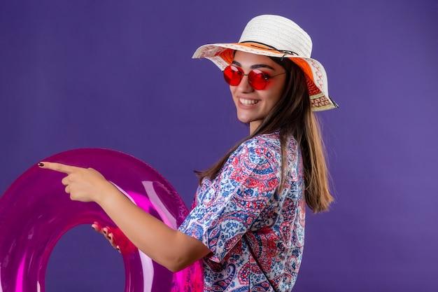 Cappello da portare di estate della giovane bella donna ed occhiali da sole rossi che tengono anello gonfiabile lateralmente che indica con il dito il lato che sorride allegramente sopra la parete viola isolata
