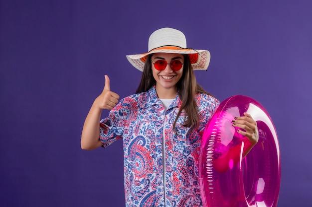 Cappello da portare di estate della giovane bella donna ed occhiali da sole rossi che tengono il fronte felice di spirito gonfiabile dell'anello che sorride allegramente mostrando i pollici su sopra la parete viola