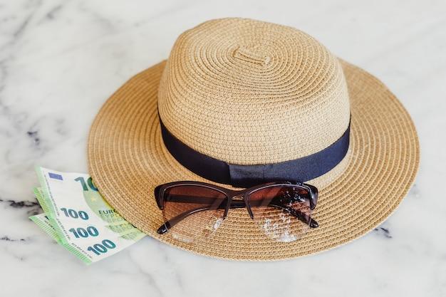 Cappello da sole con occhiali da sole e banconote in euro 100 centesimi. concetto di vacanza