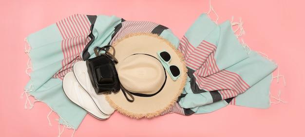 Cappello da sole e occhiali da sole in paglia sulla spiaggia rosa con spazio per il testo.