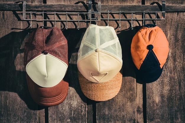 Cappello della famiglia che appende sulla parete di legno