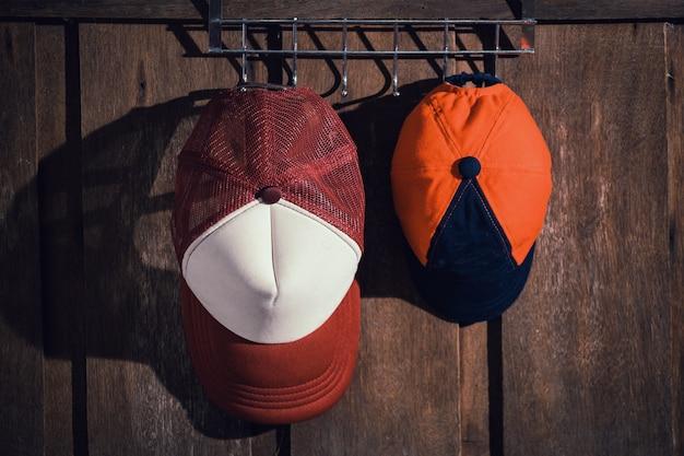 Cappello della famiglia del padre e del figlio che appendono sulla parete di legno