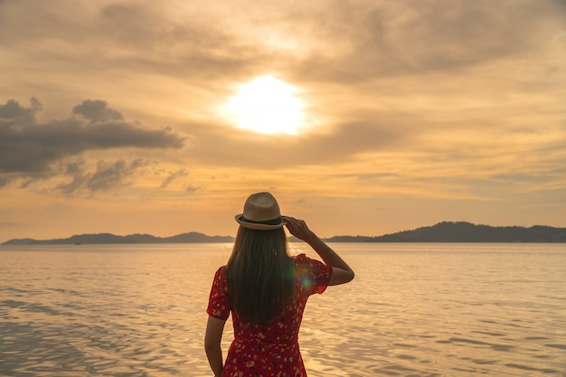 Cappello della holding della giovane donna con il tramonto
