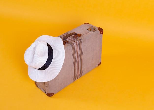 Cappello della macchina fotografica della foto della valigia, fondo giallo, concetto di viaggio
