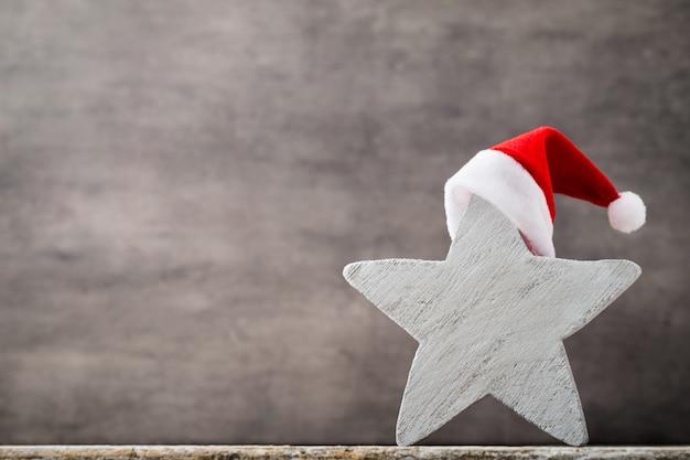 Cappello della santa delle stelle di natale. motivo natalizio. sfondo sul colore grigio.